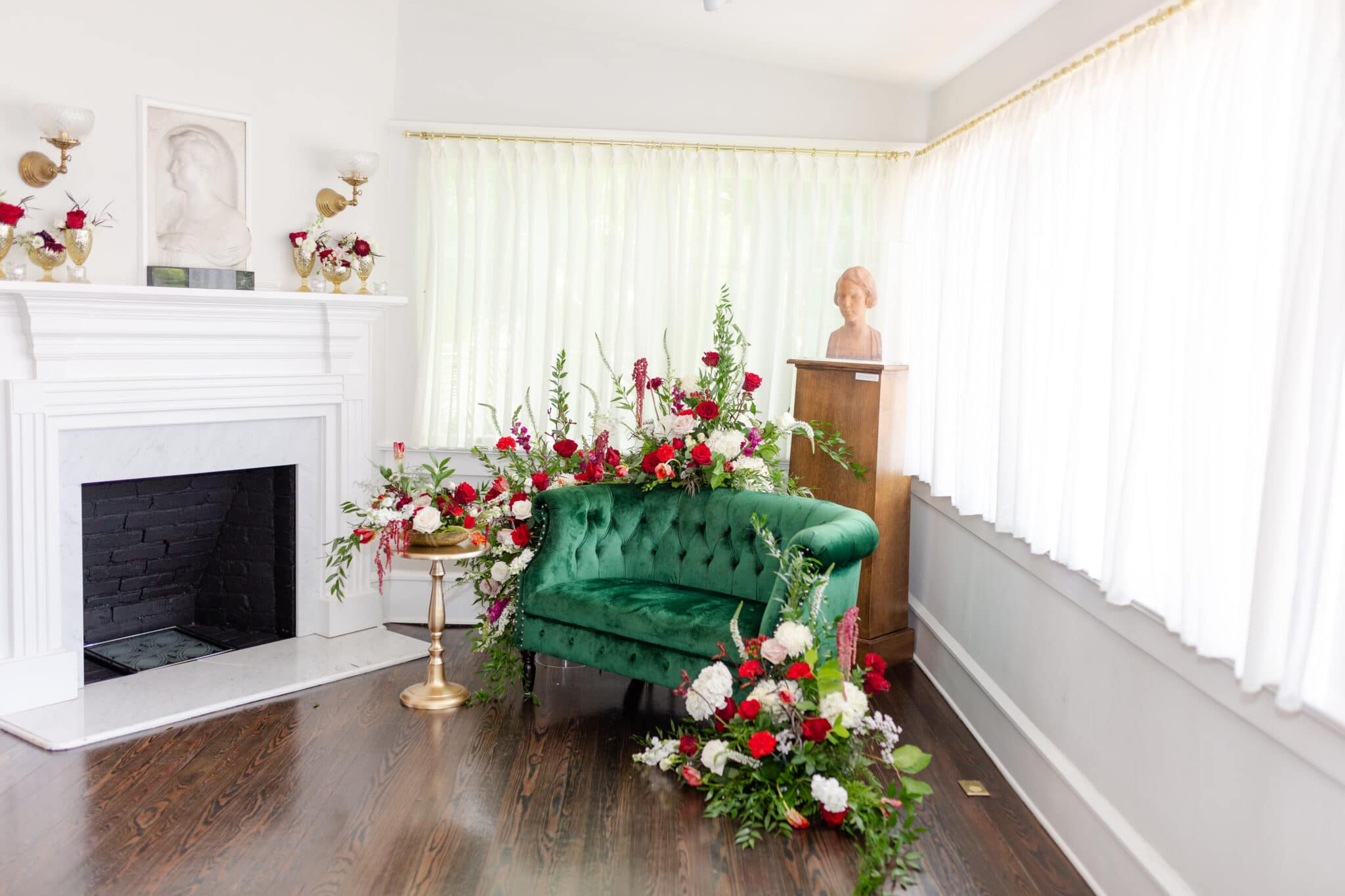 an emerald green love seat staged in the corner surrounded by red, green, and white florals with a gold side table for the christmas themed wedding inspiration shoot