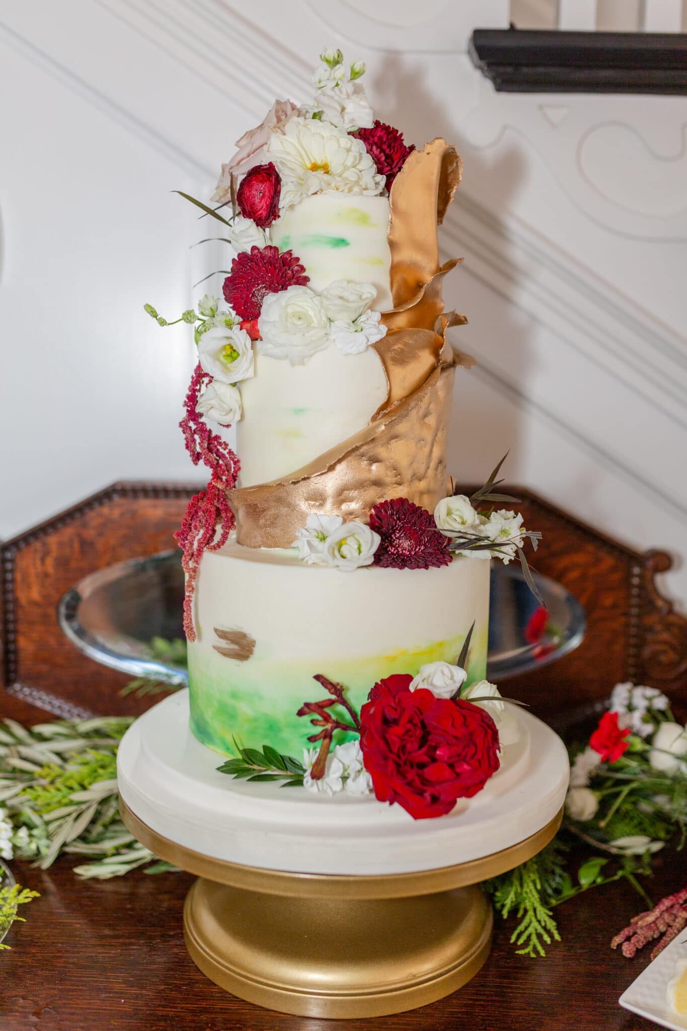 the white cake decorated with red flowers and spots of green and gold