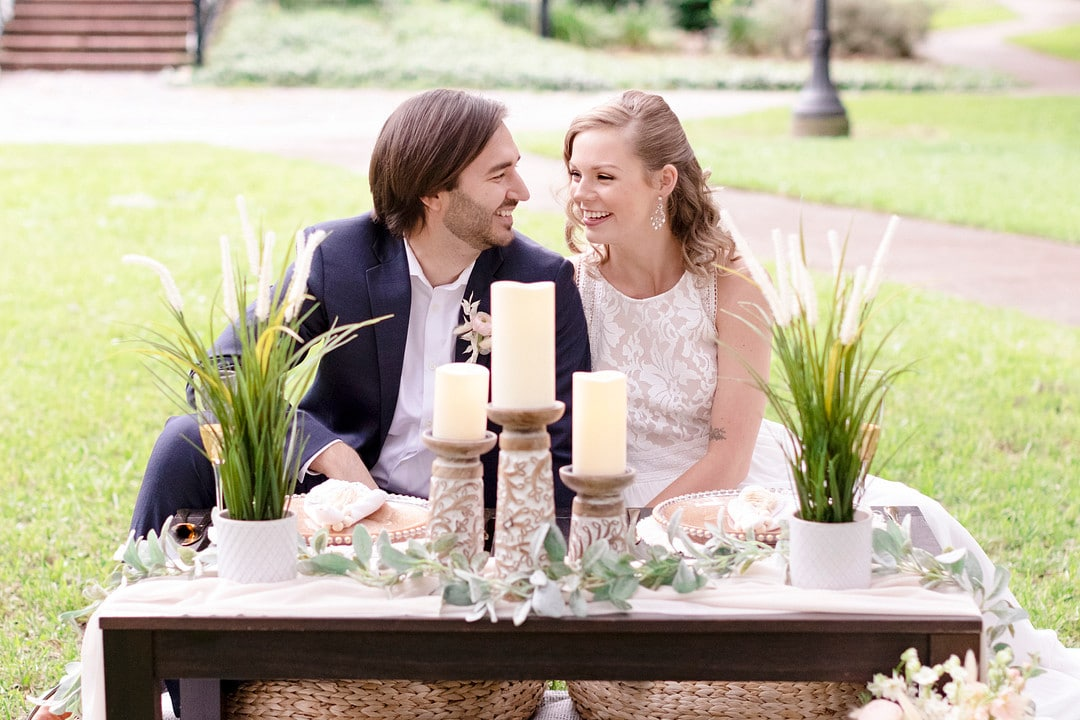 bride and groom looking at each other while sitting at their picnic set up for the picnic wedding inspiration shoot