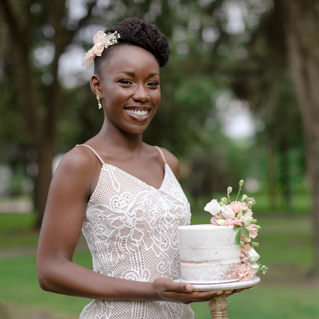 the bride smiling and holding the wedding cake for the picnic wedding inspiration shoot.