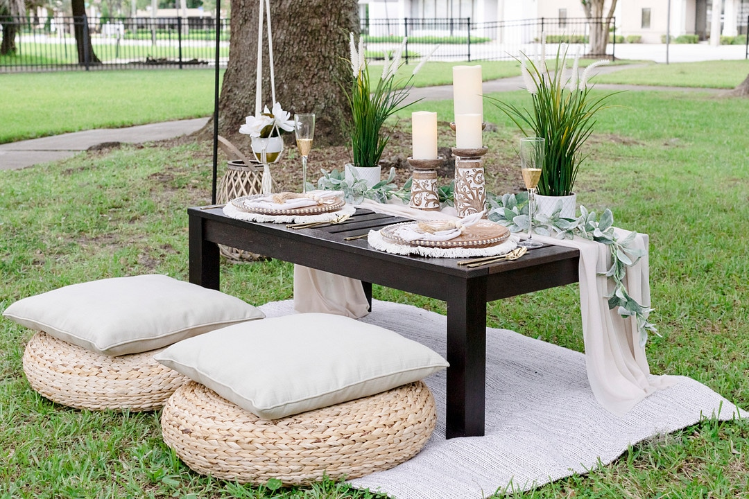 the picnic table with two dining sets, candles, pillows and florals