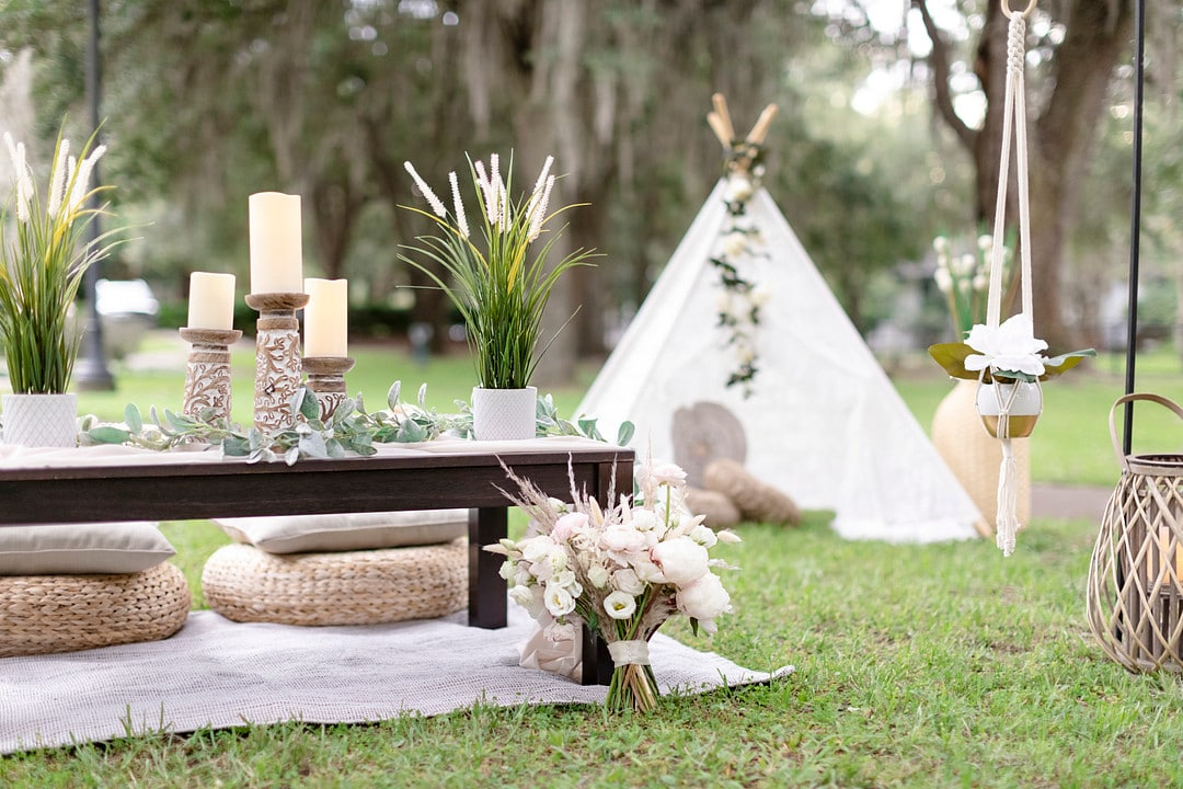 the small picnic table with decor and a white open tent in the background with white and pink florals surrounding