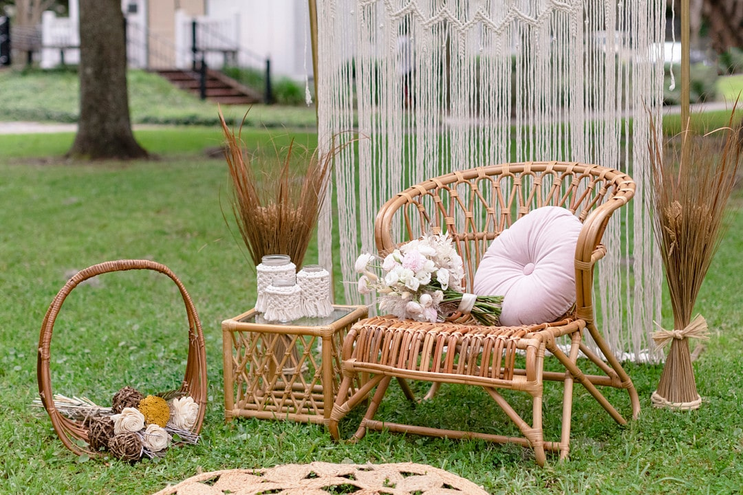 the macrame backdrop with wicker furniture decorated with pink decor