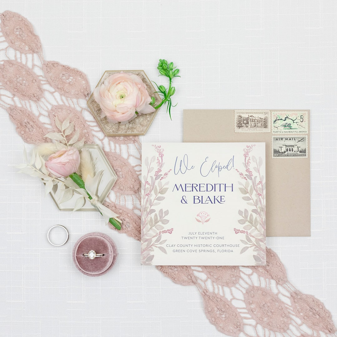 the pink and white designed invitations with florals surrounding