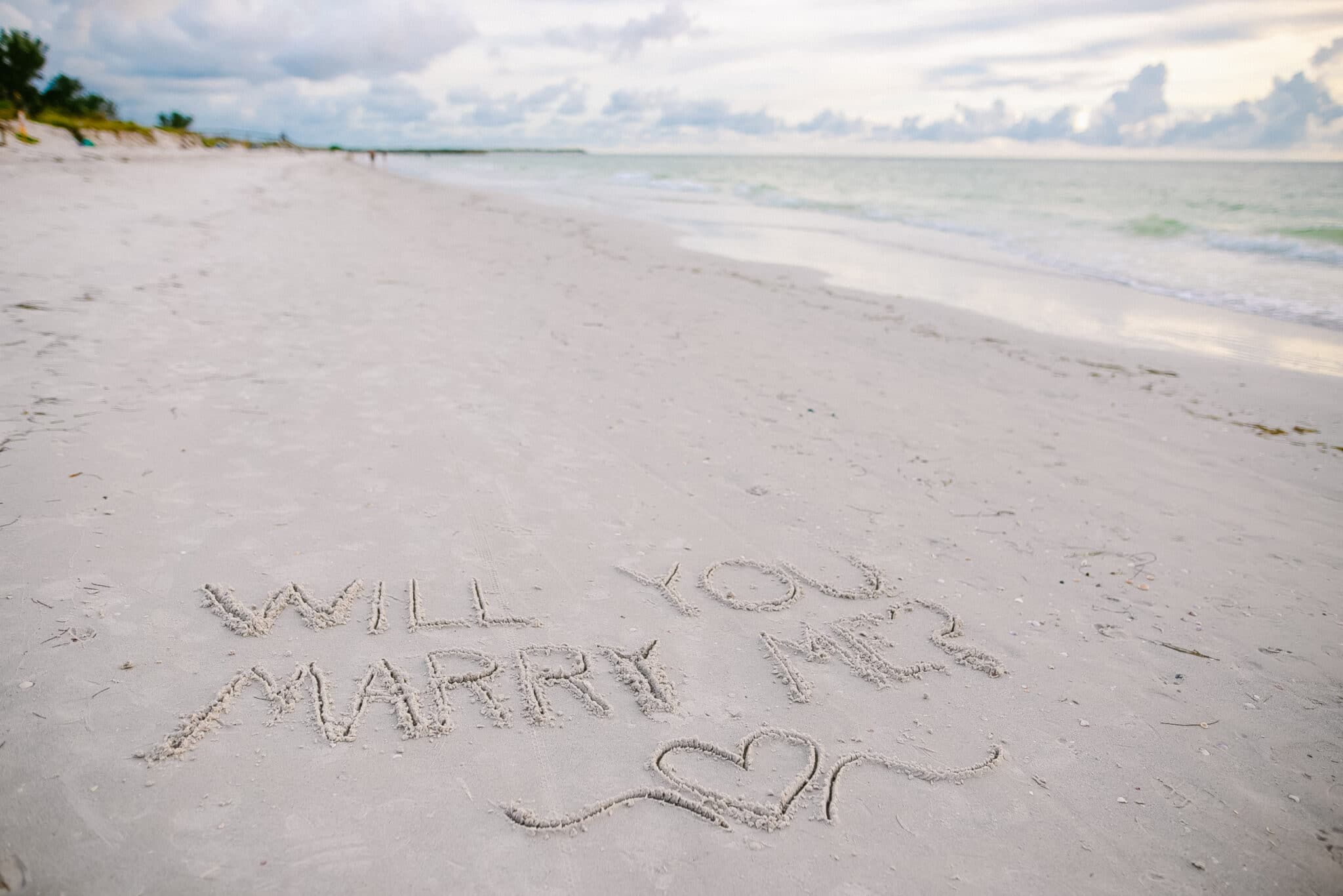 will you marry me written in the sand on the beach for the sunset at the beach marriage proposal.