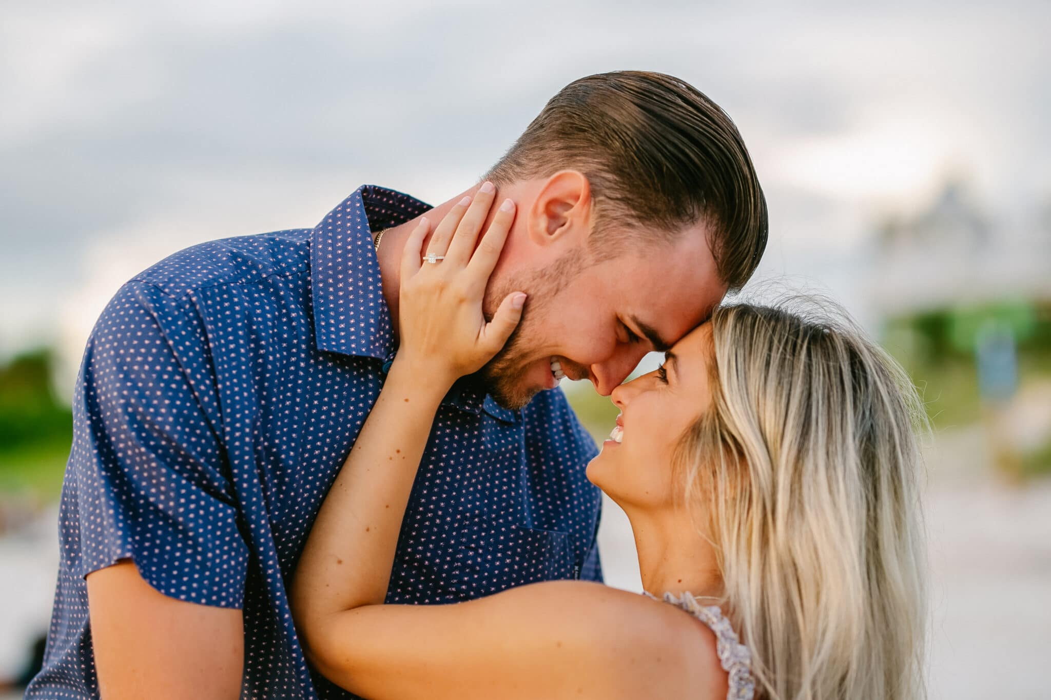 newly engaged couple forehead to forehead on the beach during the sunset after the proposal.