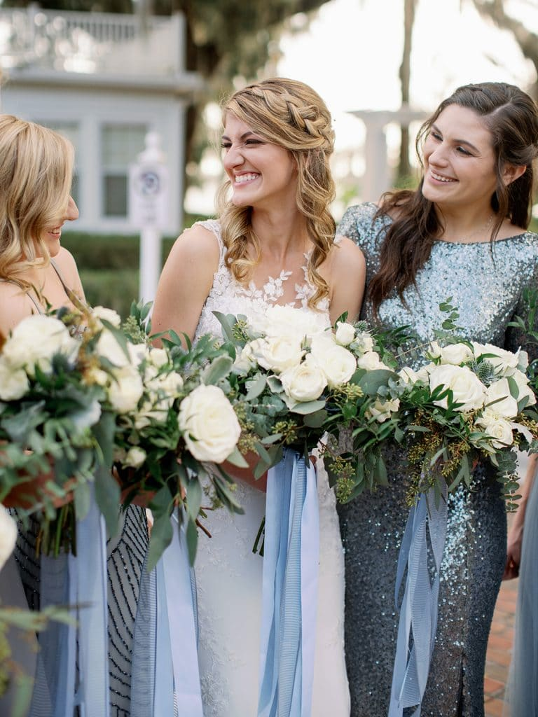 close up of bride smiling while holding bouquet with long blue ribbon and bridesmaids holding bouquets next to her with similar styles
