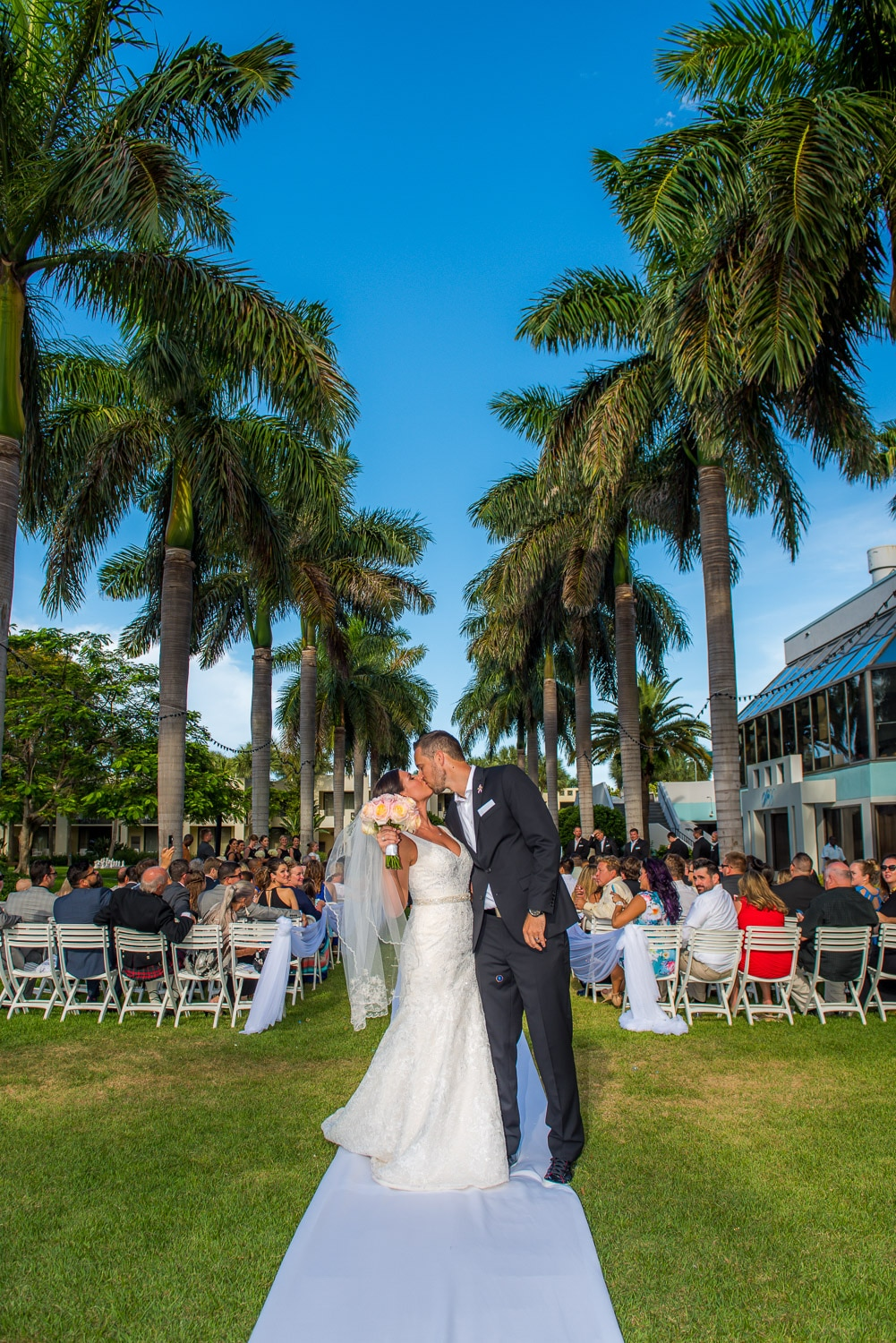 Bride and Groom kissing with palm aisle