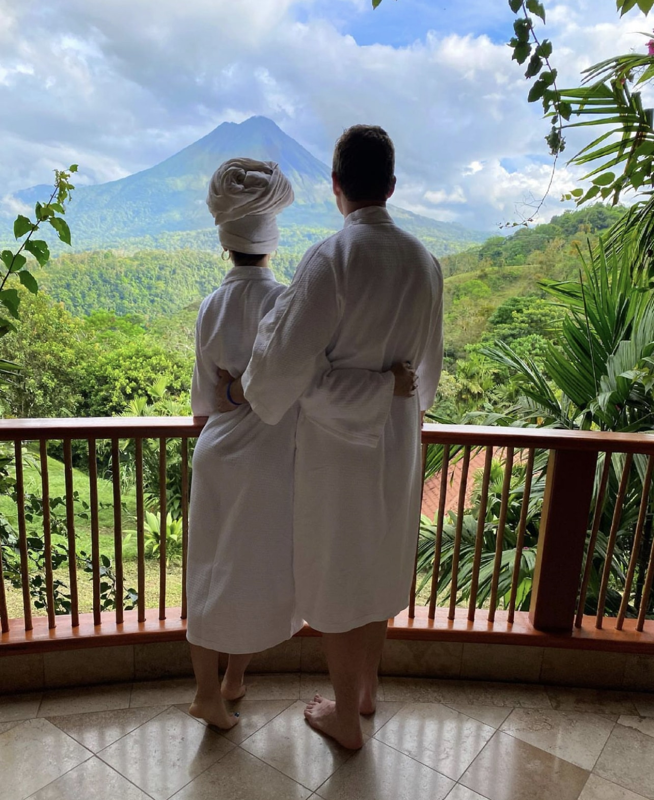 bride and groom to be wearing matching robes and looking out over the tropical location