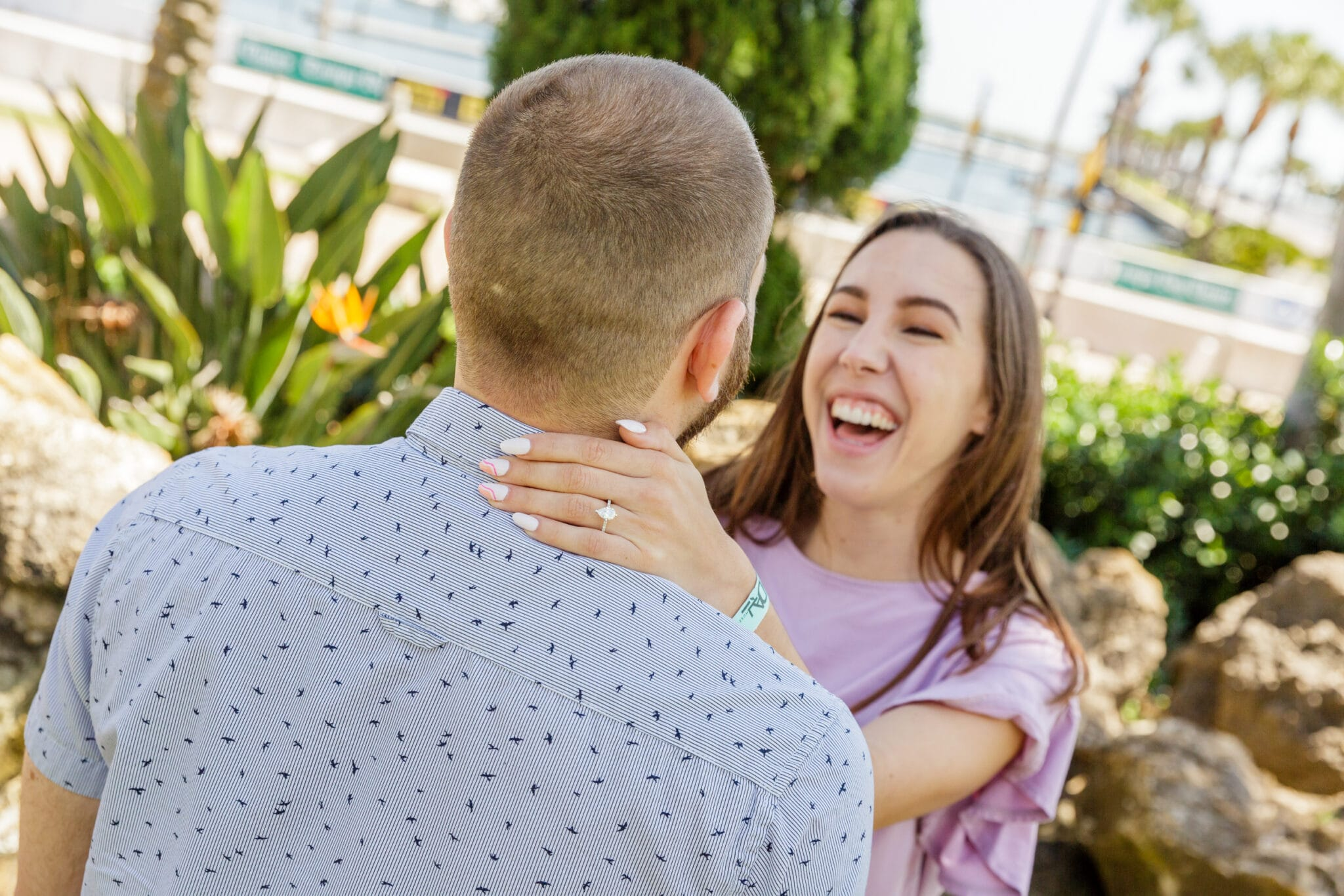 bride to be with her left hand with new ring behind her future husband's neck