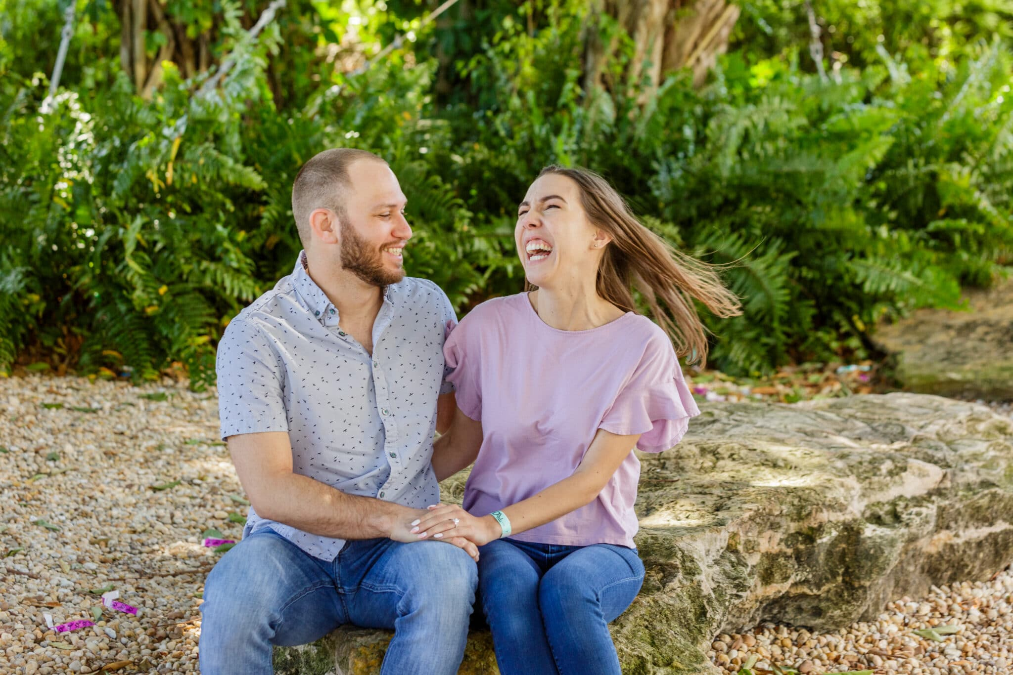 bride and groom to be sitting on a rock with bushes in the background holding hands and laughing