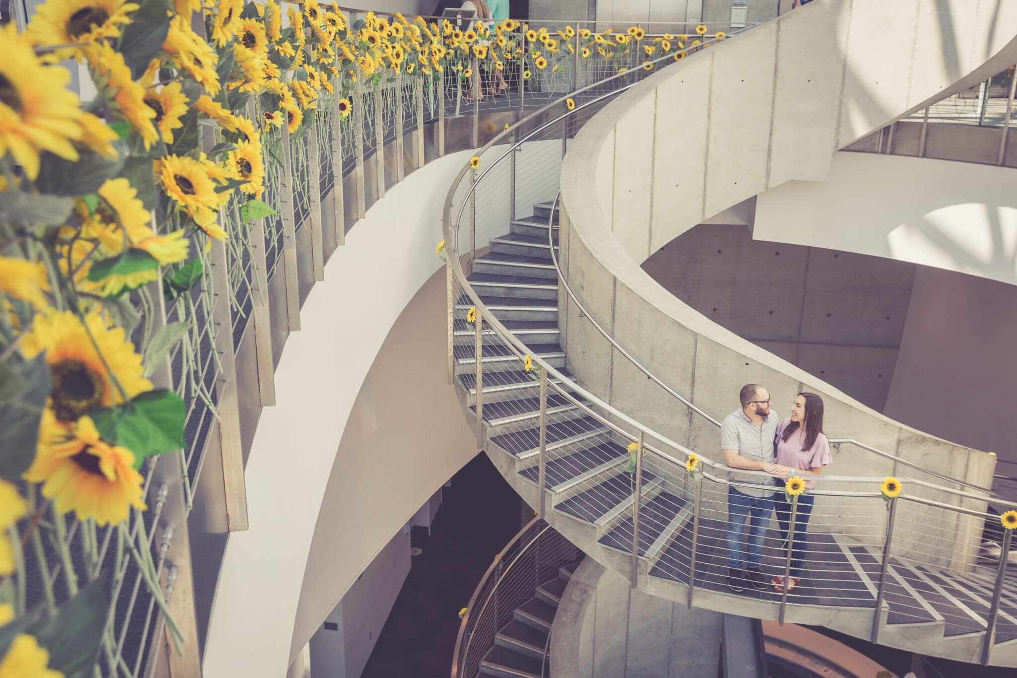 bride and groom to be looking at each other and smiling on the spiral stair case decorated with sunflowers