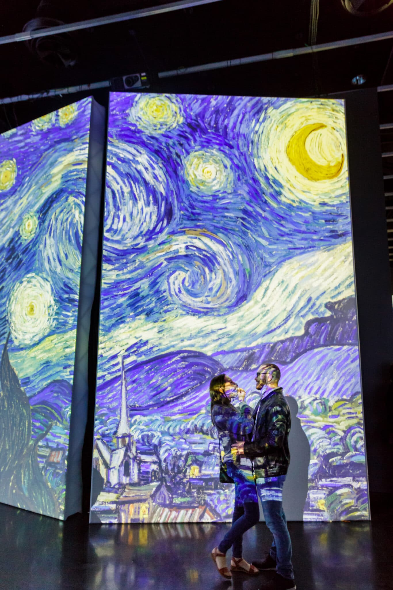 couple hugging in front of van gogh starry night after the salvador dali museum marriage proposal