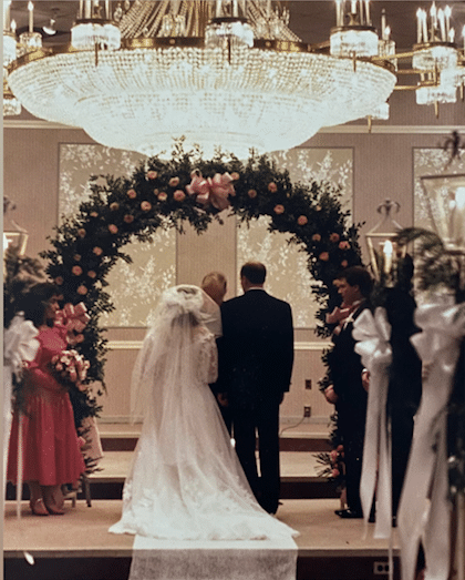 Bride and Groom under huge chandelier and arch