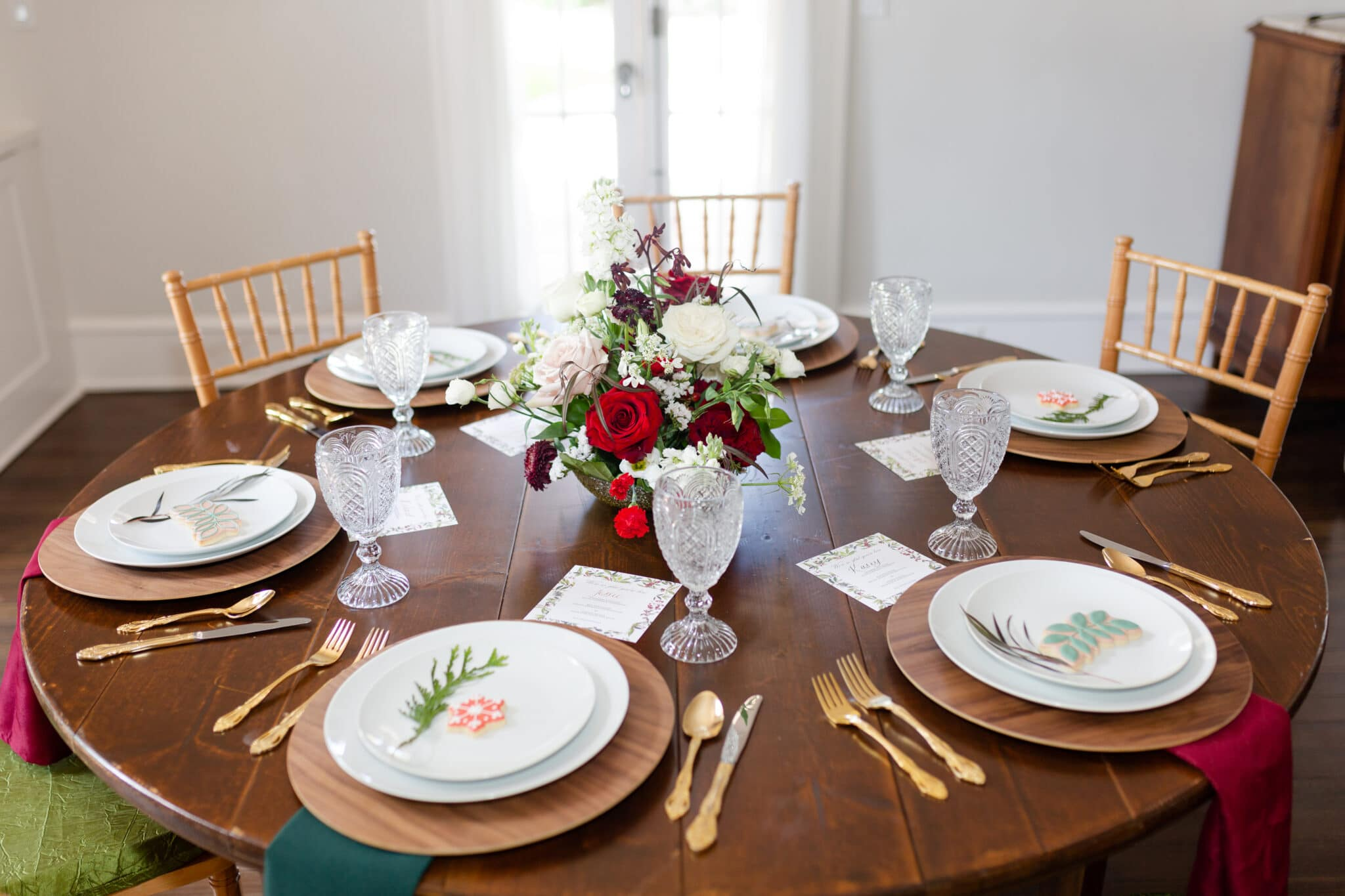 a large round table set for six people with Christmas themed wedding inspiration of red, green, white and gold accents