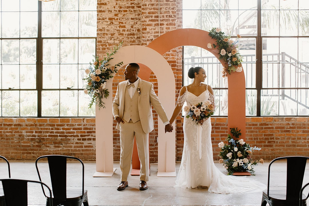 bride and groom holding hands in their ceremony space looking away from each other.