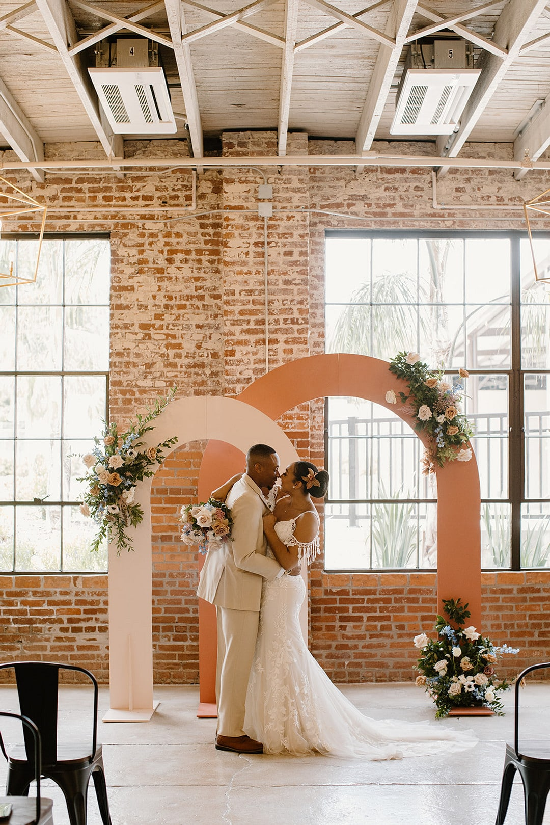 bride and groom holding each other at the end of the aisle in front of the two large pink arches for the urban loft wedding inspiration styled shoot.