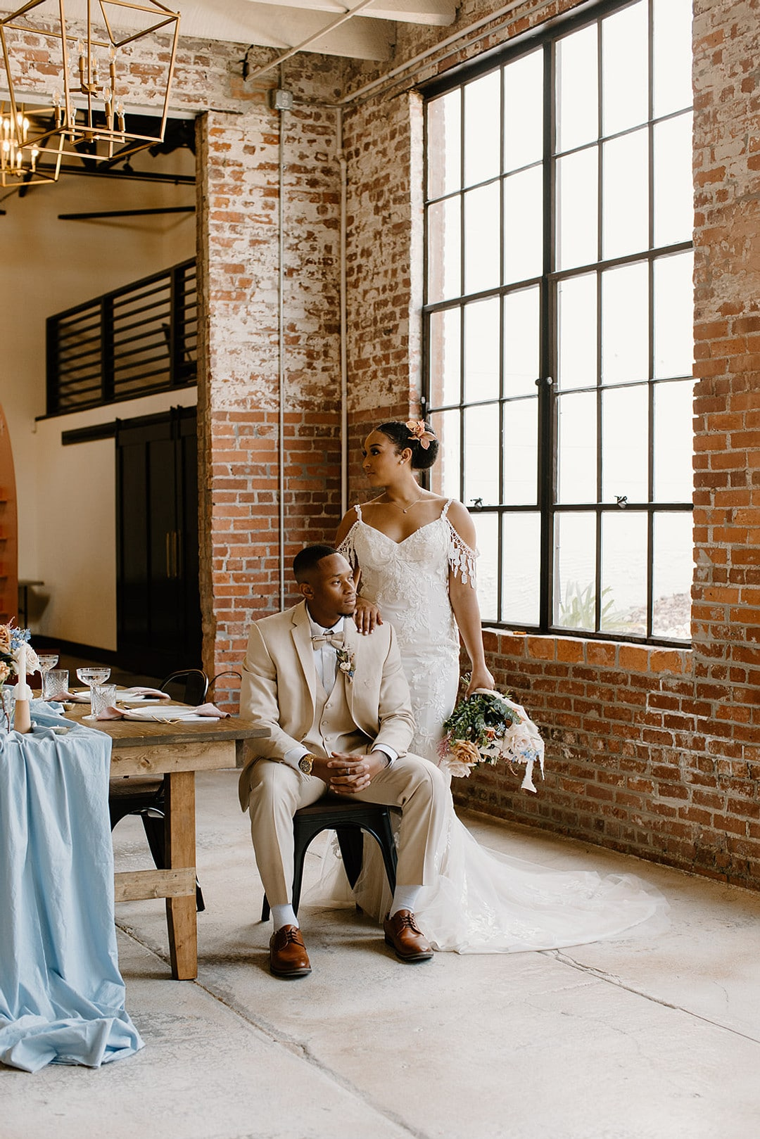 groom sitting down and bride standing behind him at their reception table.