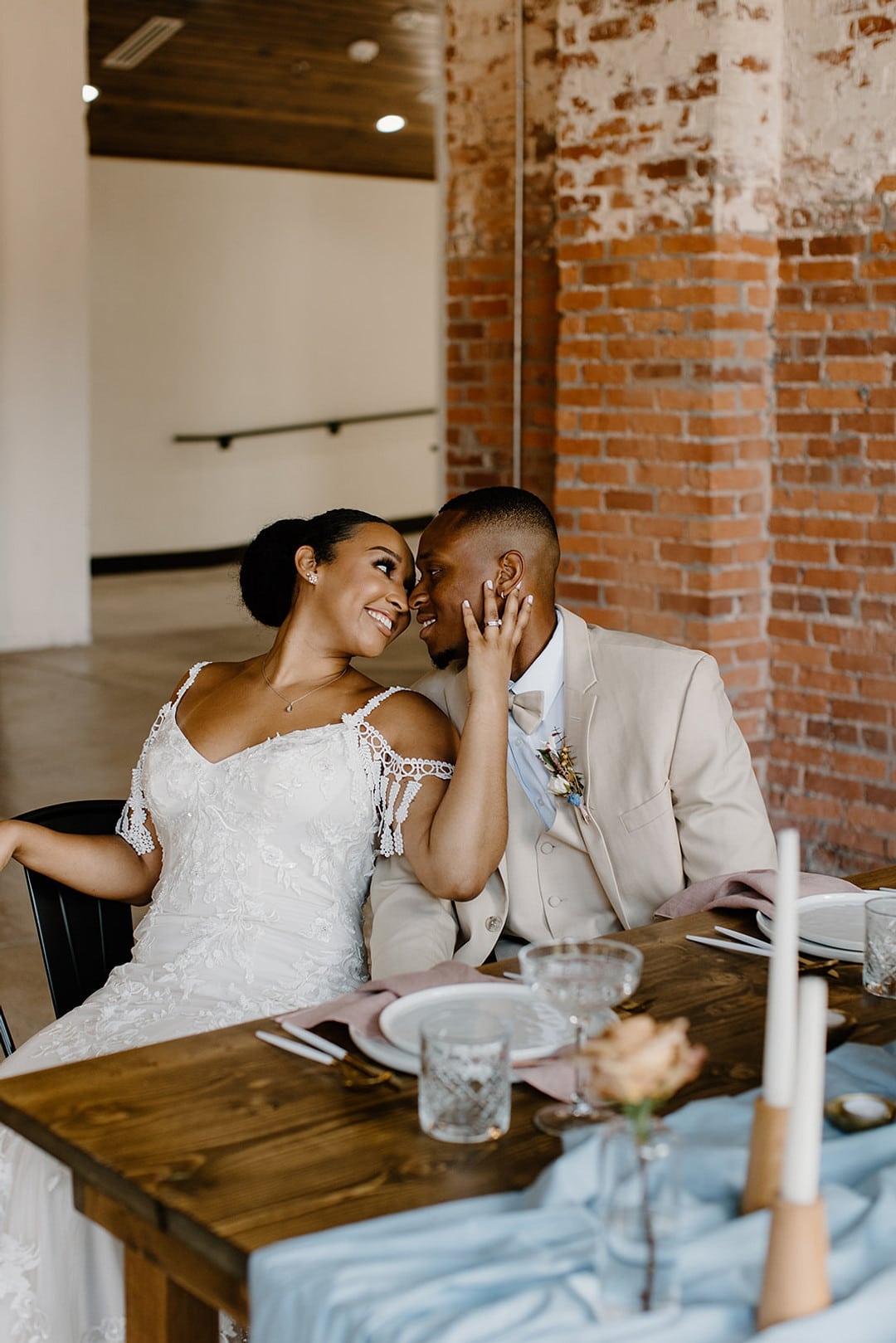bride holding the grooms face as they are sitting at the reception table.