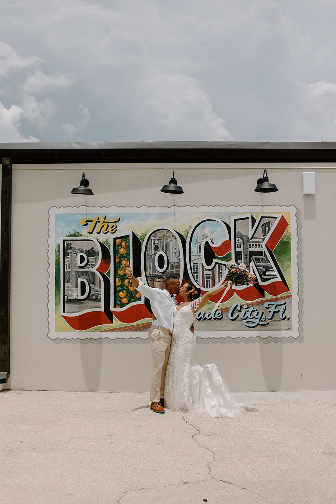 bride and groom kissing in front of venue at the block sign for the urban loft wedding inspiration shoot.