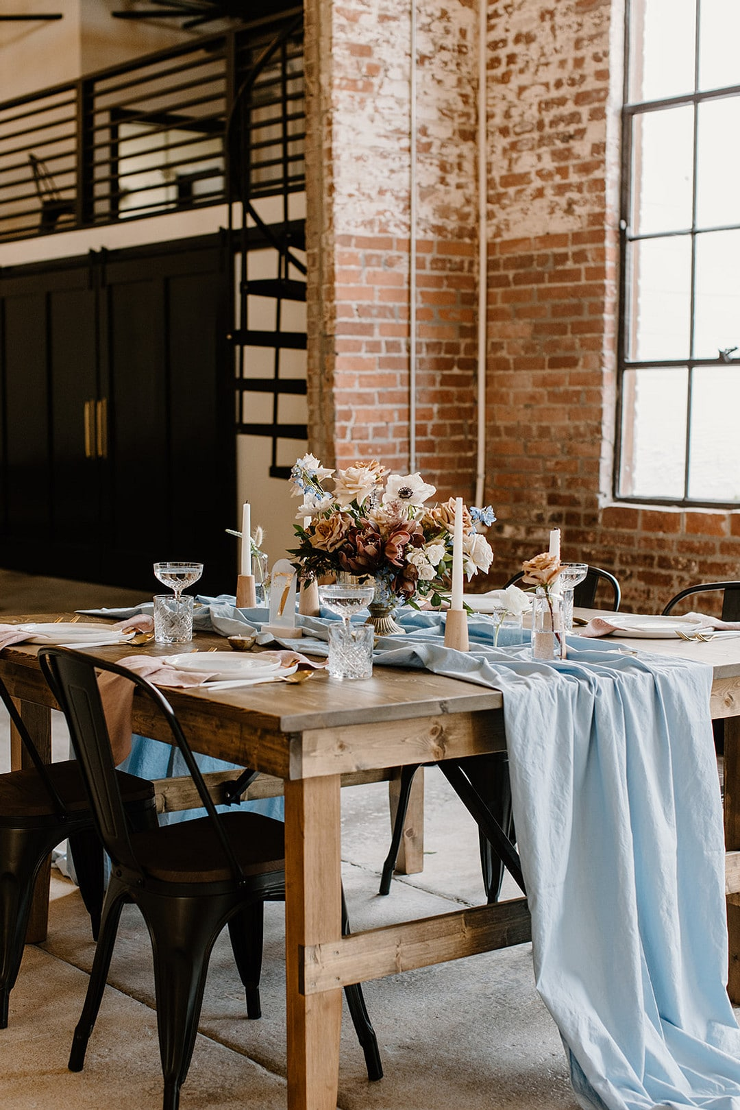 the reception table set up for the urban loft wedding inspiration with blues and pinks and other natural tones.