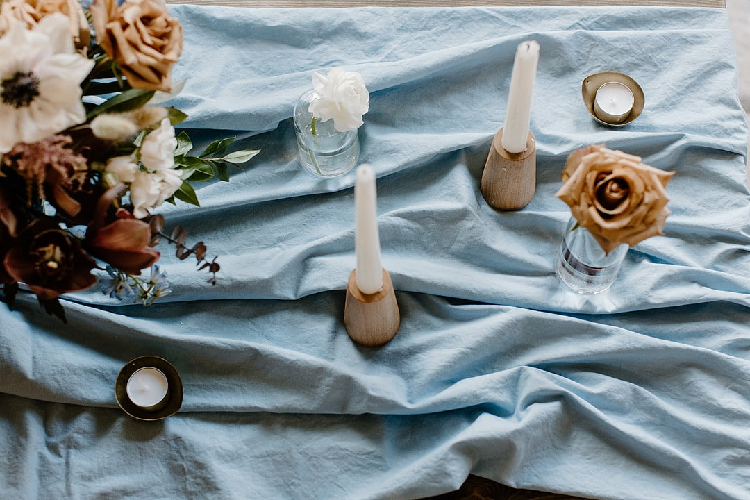 blue tablecloth with candles and vases with singular flowers and a large flower centerpiece.