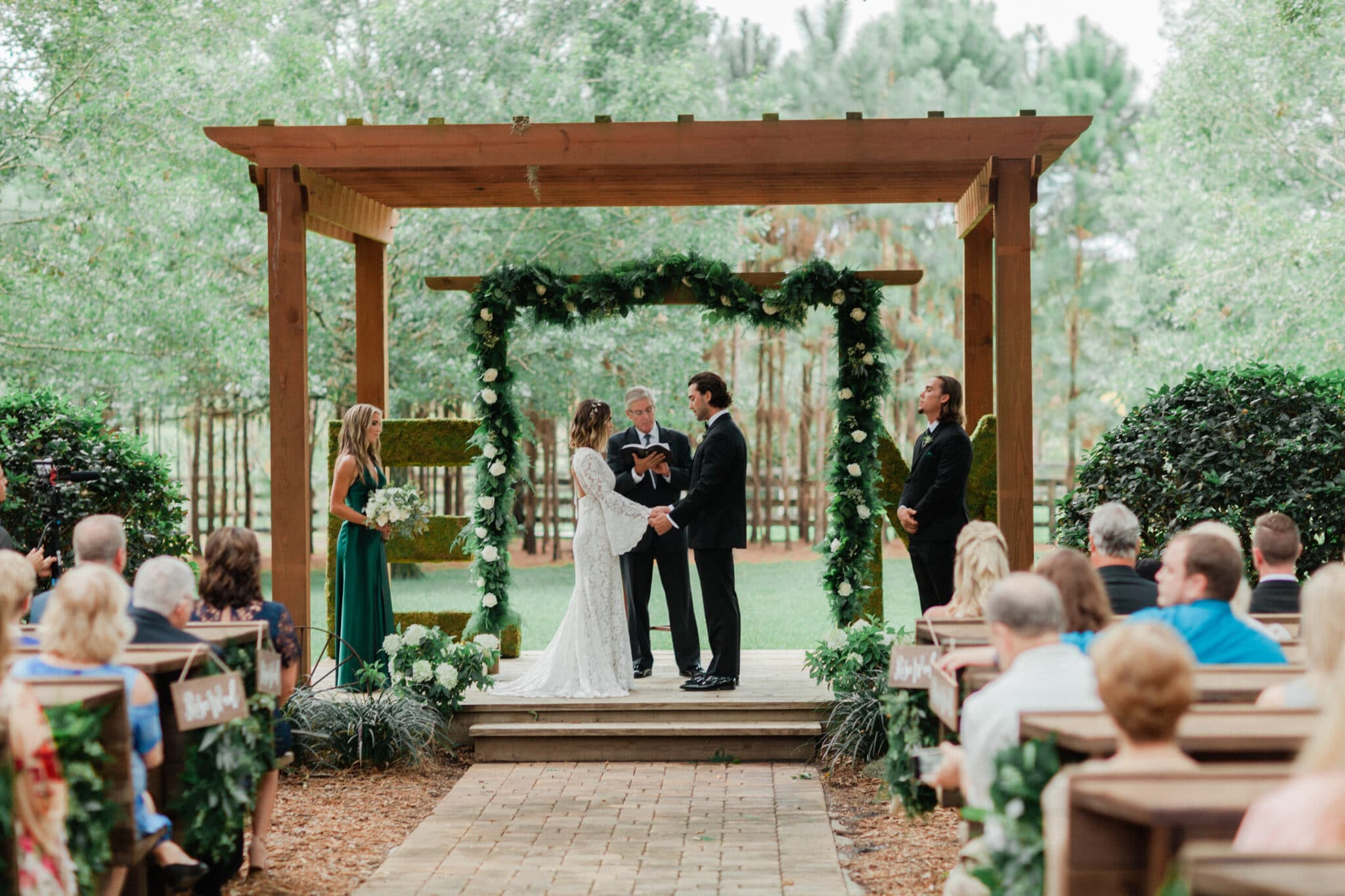green garland with white flowers used as arch behind couple during wedding ceremony