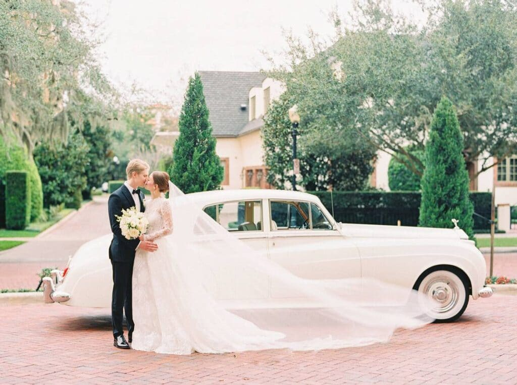 bride and groom kissing next to classic car