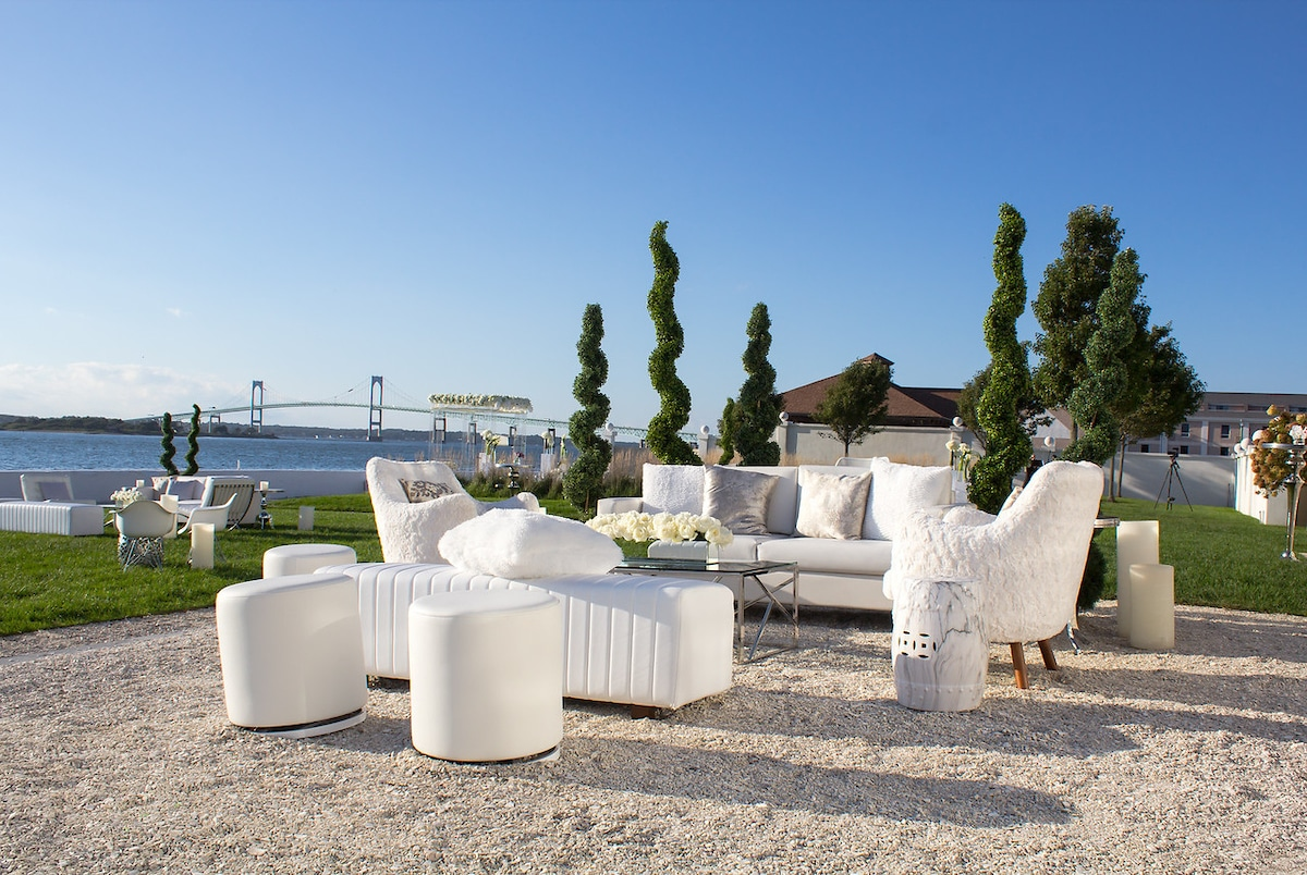 Outdoor wedding lounch with surround trees. There's a large bridge behind it.